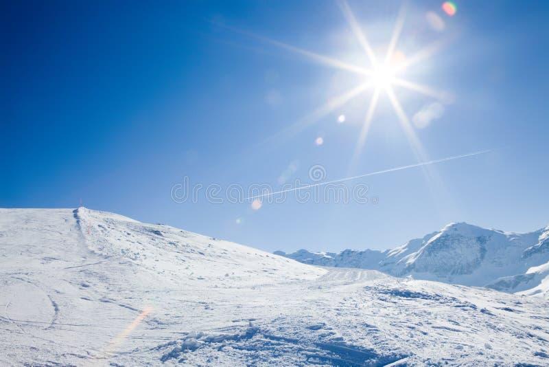 Zon over de winterbergen stock afbeelding