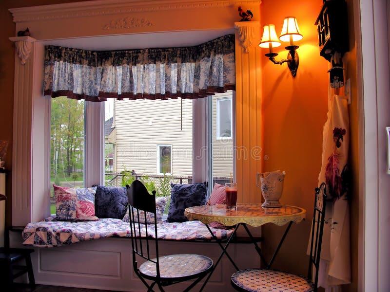 Zona de desayuno acogedora en ventana salediza brillante imagenes de archivo