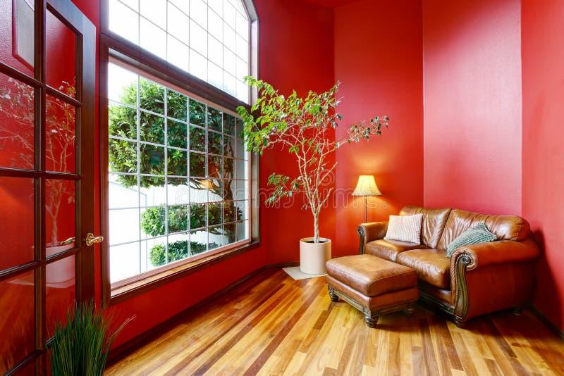 Zona de descanso con las paredes rojas, la ventana grande y el sofá del cuero imágenes de archivo libres de regalías