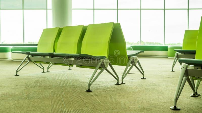 Zona de espera vacía del terminal de aeropuerto con las sillas verdes foto de archivo