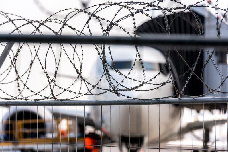 Zona de segurança aeroportuária Aviões borrados atrás de uma cerca do arame farpado Ilustração do incidente no transporte da avia foto de stock royalty free