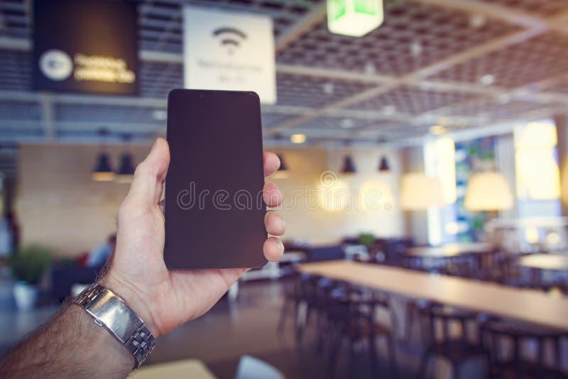 Zona franca di Wifi Lo smartphone moderno nero dentro equipaggia la mano contro il fondo del caffè Zona di Wi-Fi in caffè I Wi fi fotografia stock libera da diritti