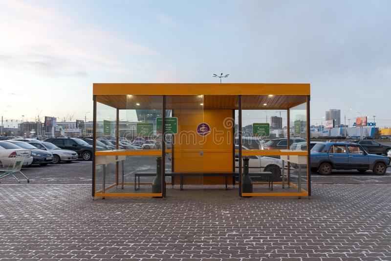 Zona fumatori specialmente fornita sui precedenti di parcheggio, nella sera fotografia stock