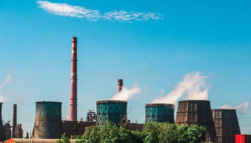 Zona industriale, centrale elettrica con i camini di fumo o fabbrica fabbricante, fumaioli enormi con vapore come inquinamento de immagini stock libere da diritti