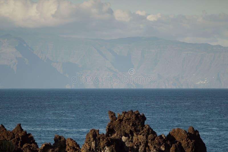 Zona oriental de la isla de Gomera del La vista de Tenerife Tiro largo de la lente Cielo azul con las nubes, agua azul bajo línea foto de archivo libre de regalías