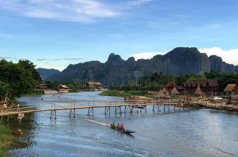 Zona rurale nel Laos con il ponte di legno e di bambù che attraversa il ri fotografia stock