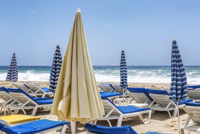 Zonbedden met paraplu's op een openbaar zandig strand Close-up royalty-vrije stock foto's
