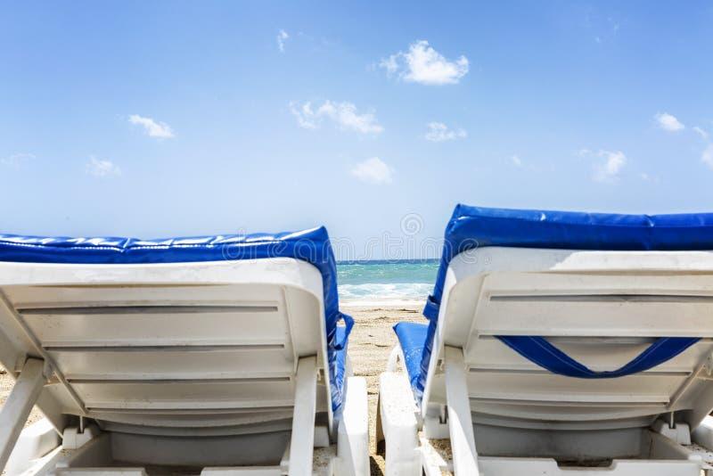Zonbedden op het strand tegen het blauwe overzees Close-up Ruimte voor tekst stock afbeelding