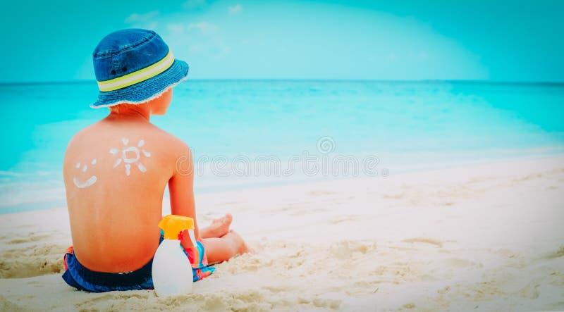 Zonbescherming weinig jongen met suncream bij strand royalty-vrije stock foto