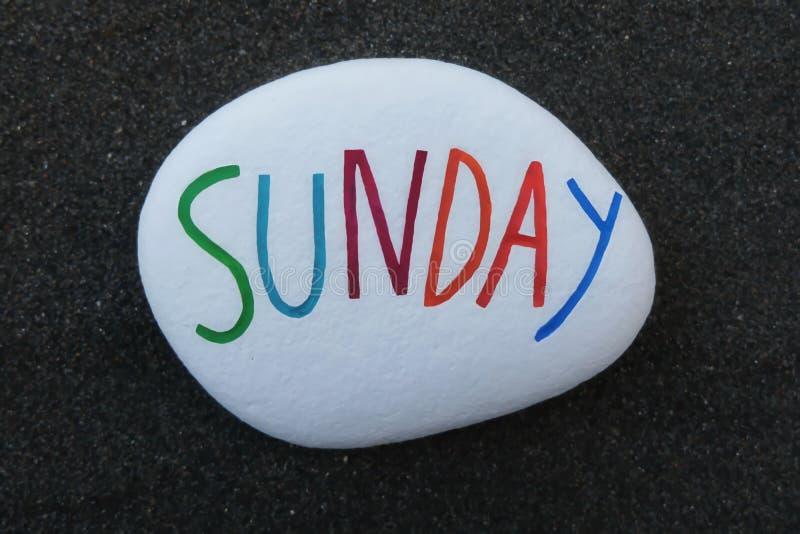 Zondag, sneed de zevende dag van de week en schilderde op een witte steen over zwart vulkanisch zand royalty-vrije stock foto