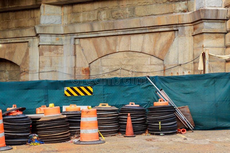 Zone de construction avec les marqueurs oranges de précaution le long d'une rue urbaine images stock