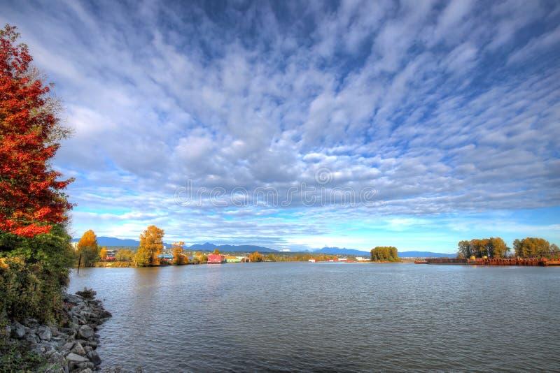 Zone industrielle par une rivière avec des couleurs d'or de chute images stock