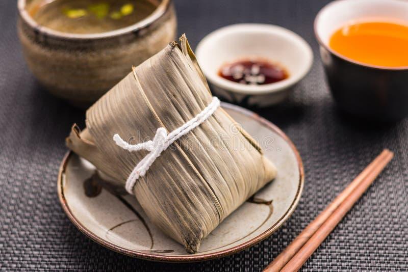 Zongzi eller asiatiska kinesiska klimpar för klibbiga ris med gult te, s fotografering för bildbyråer