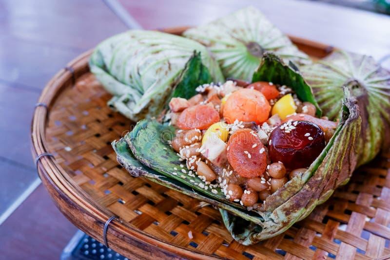 Zongzi glutinous ryż zawijający w Lotosowym liściu stawiającym na omłotowym koszu zdjęcie stock