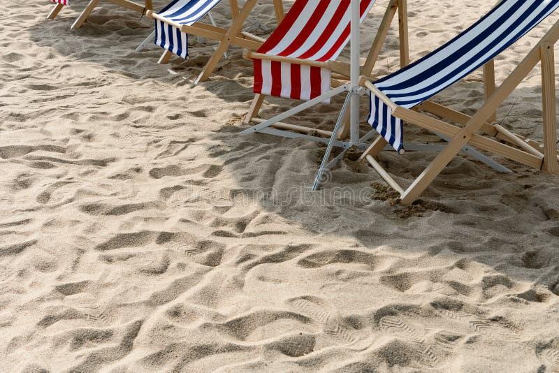 Zonlanterfanters in de schaduw op zand stock foto