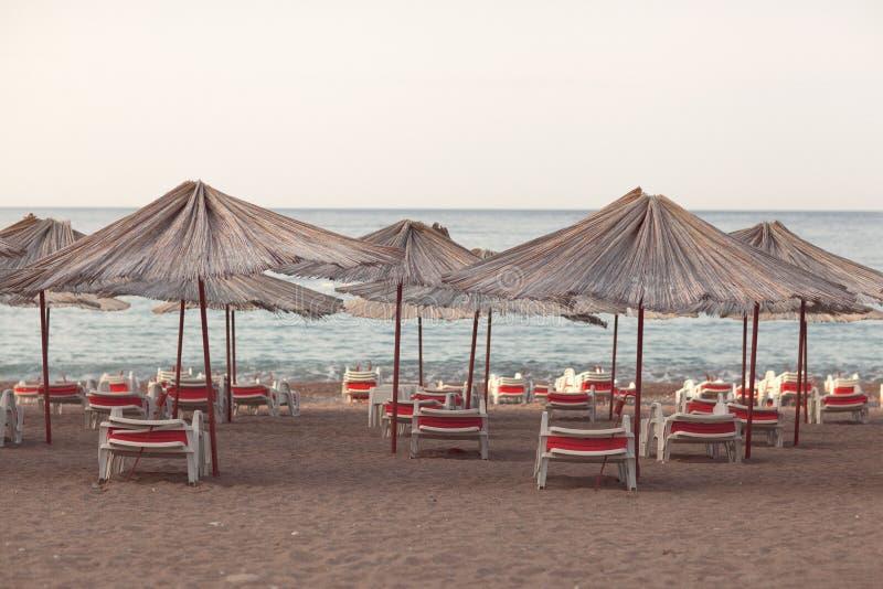 Zonlanterfanters met een paraplu op het strand die het overzees overzien royalty-vrije stock foto