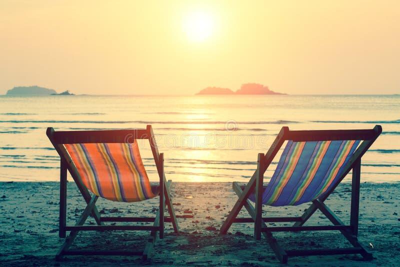 Zonlanterfanters op het overzeese strand ontspan stock afbeeldingen