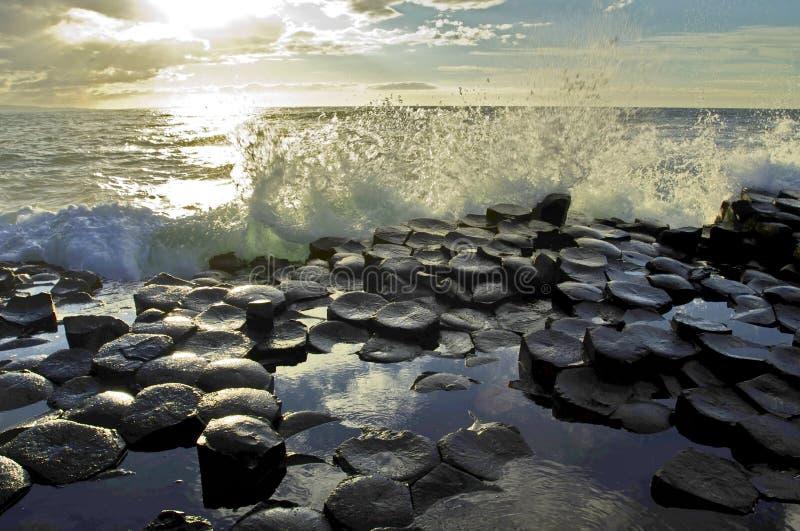 Zonlicht die golven benadrukken die op de hexagonale Basaltplakken verpletteren van Reuzenverhoogde weg royalty-vrije stock foto