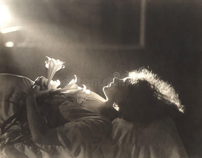 Zonlicht die op vrouw met bloemen vallen die in bed slapen royalty-vrije stock foto's