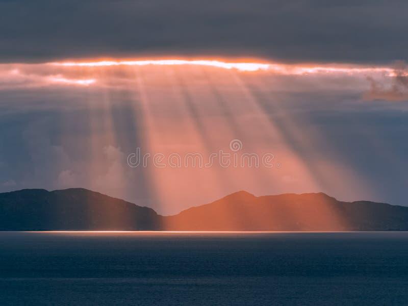 Zonlicht het richten door de donkere wolken bij zonsondergang stock fotografie