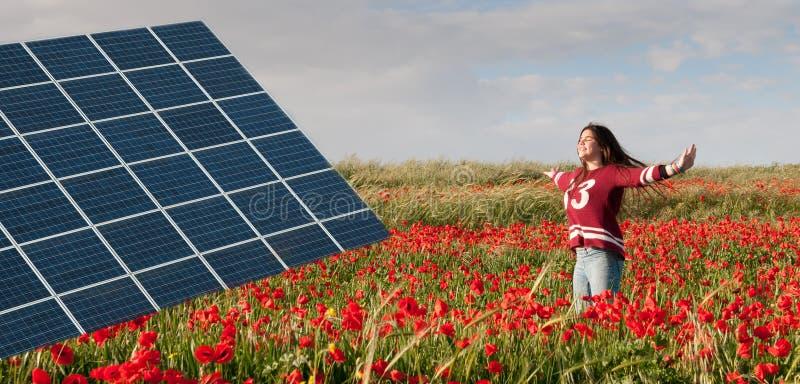 Zonne-energiepaneel en tiener op een gebied met rode papavers stock afbeeldingen