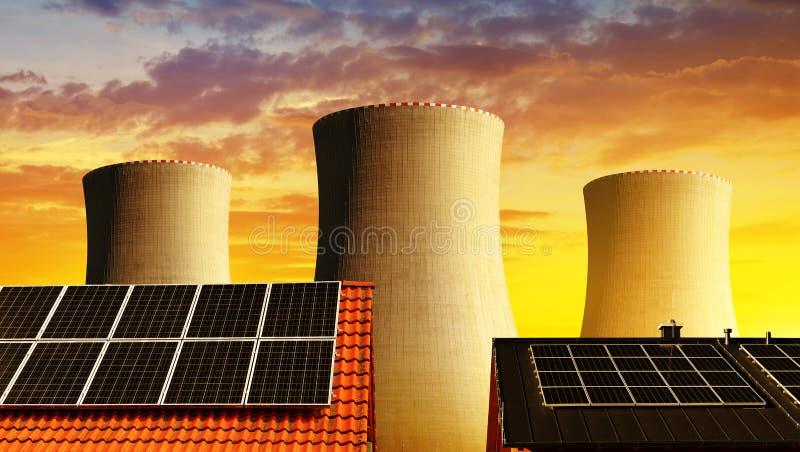 Zonne-energiepaneel op het dak van het huis in de koeltorens als achtergrond van kernenergieinstallatie stock afbeelding