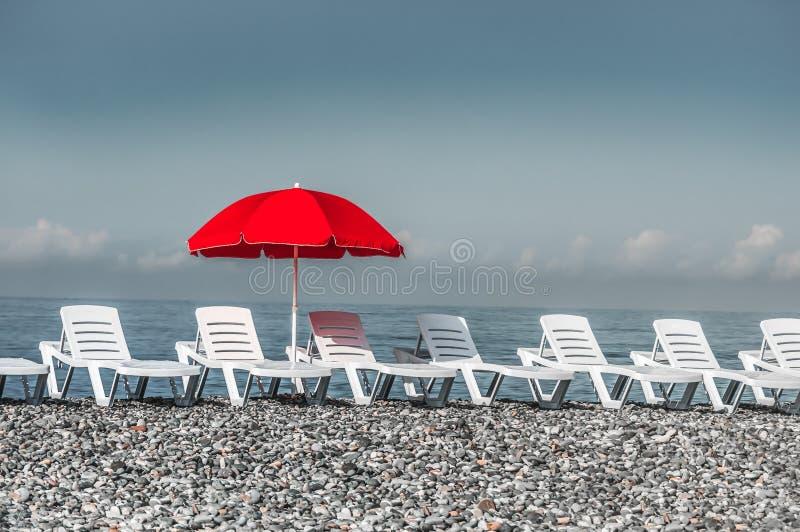Zonnebadende plastic bedden en rode paraplu op het strand stock fotografie