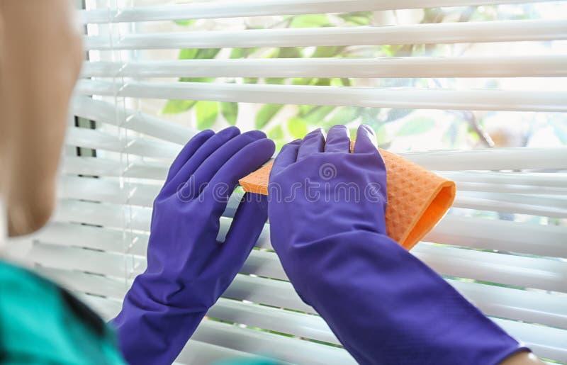 Zonneblinden van het vrouwen de schoonmakende venster met vod binnen stock afbeeldingen
