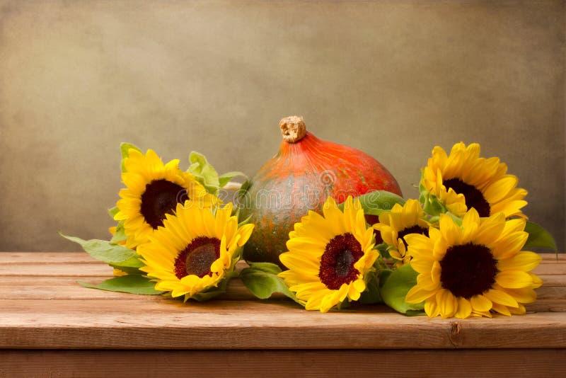 Zonnebloemen en pompoen op houten lijst royalty-vrije stock afbeeldingen