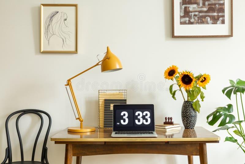 Zonnebloemen, gele lamp en laptop op houten bureau in het binnenland van het huisbureau met affiches Echte foto stock afbeelding