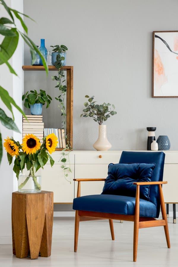 Zonnebloemen op houten kruk naast blauwe leunstoel in woonkamerbinnenland met affiche Echte foto stock foto