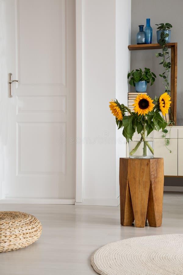 Zonnebloemen op houten kruk naast poef in wit woonkamerbinnenland met deur en deken Echte foto royalty-vrije stock fotografie