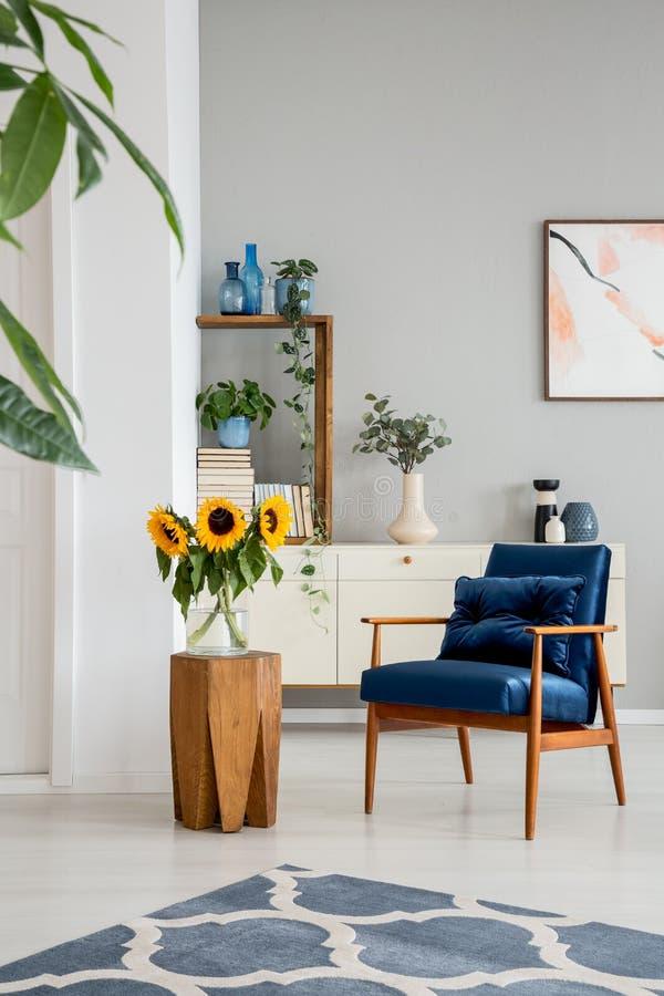 Zonnebloemen op houten lijst naast blauwe leunstoel in grijs binnenland met affiches en tapijt stock afbeeldingen
