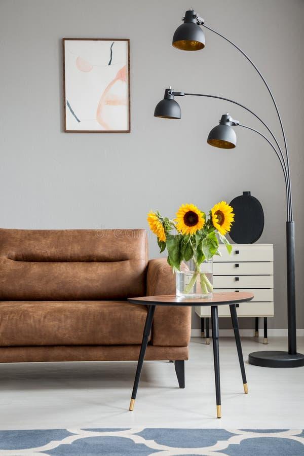 Zonnebloemen op houten lijst naast bruine bank en zwarte lamp in vlak binnenlands met affiche Echte foto royalty-vrije stock afbeeldingen
