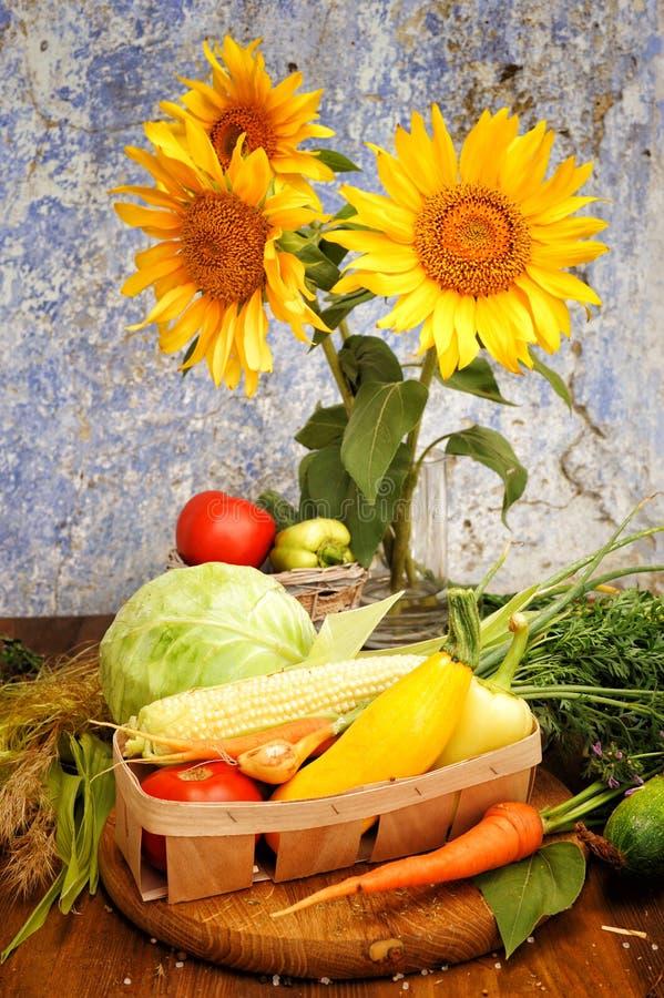 Zonnebloemenboeket en geassorteerde verse groenten in een mand stock afbeelding