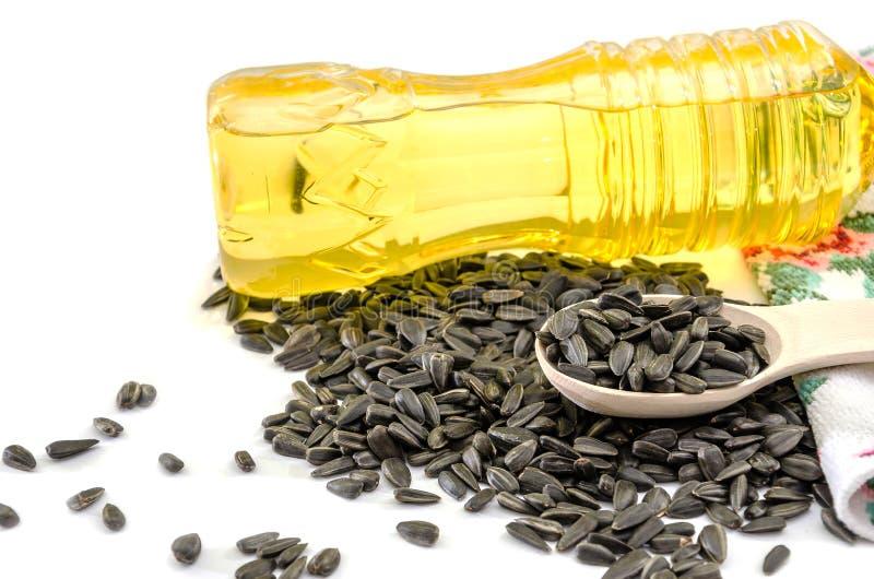 Zonnebloemolie in een fles en zaden op een houten lepel op een witte achtergrond royalty-vrije stock foto's