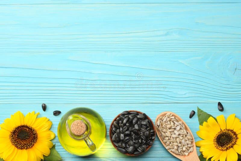 Zonnebloemolie in glaskruik, zaden en bloem op blauwe houten achtergrond Hoogste mening met exemplaarruimte stock foto