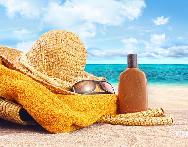 Zonnebrandolie, strohoed bij het strand royalty-vrije stock foto