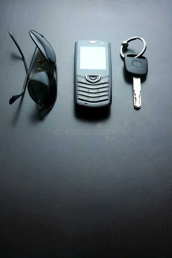Zonnebril, autosleutel en cellphone op een houten lijst stock afbeeldingen