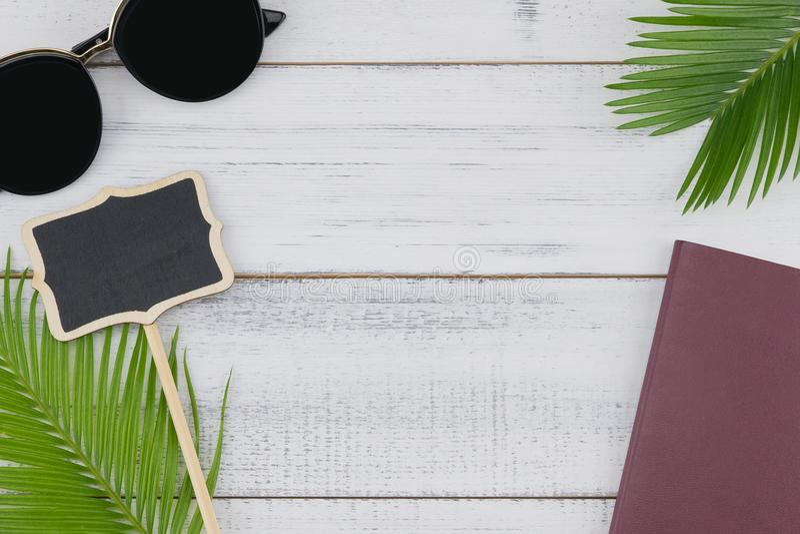 Zonnebril, leeg klein raad en paspoort met varenbladeren royalty-vrije stock foto's