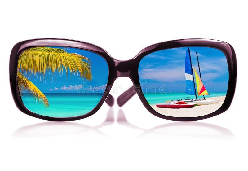 Zonnebril met strand dat het glas wordt overdacht stock fotografie