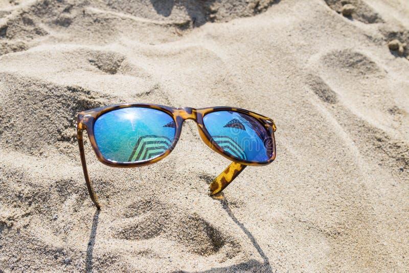 Zonnebril op strand stock foto