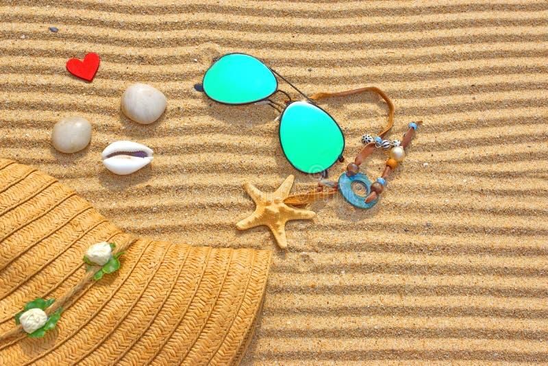Zonnebril, Straw Hat en verschillende voorwerpen op het strandzand stock afbeelding