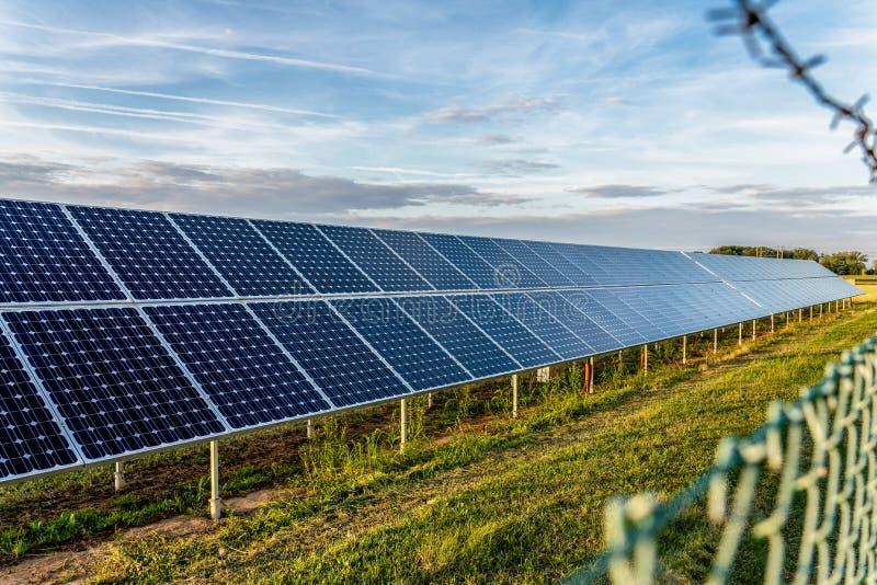 Zonnelandbouwbedrijf met photovoltaic panelen achter de omheining met prikkeldraad stock fotografie