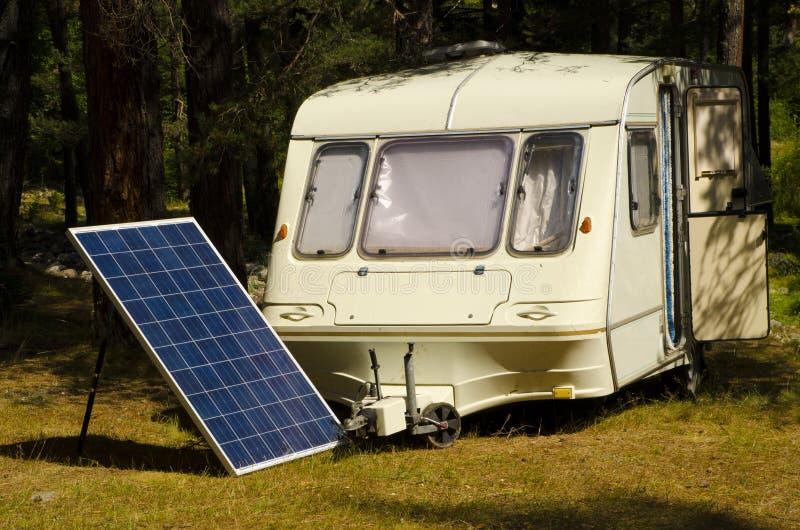 Zonnepaneel in het kamperen met oude caravan op de rivierbank royalty-vrije stock afbeeldingen