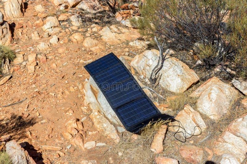 zonnepaneel in kampeerterrein op een rots om telefoons en camera, alternatieve elektriciteitsbron te laden - concept duurzame mid stock fotografie