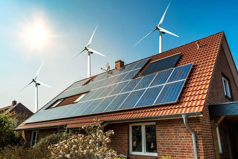 Zonnepaneel op een dak van een huis en een wind turbins arround royalty-vrije stock fotografie