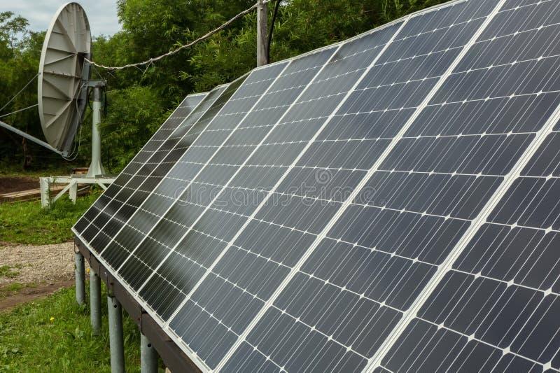 Zonnepanelen en satellietschotel voor energie en mededeling in voorsteden stock afbeeldingen