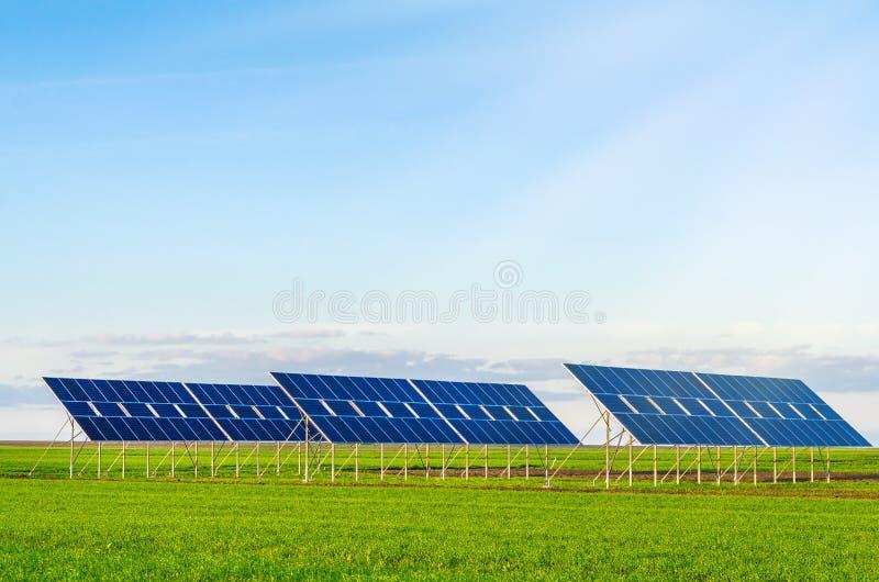 Zonnepanelen op een gebied op groen gras Milieuvriendelijk stock afbeelding