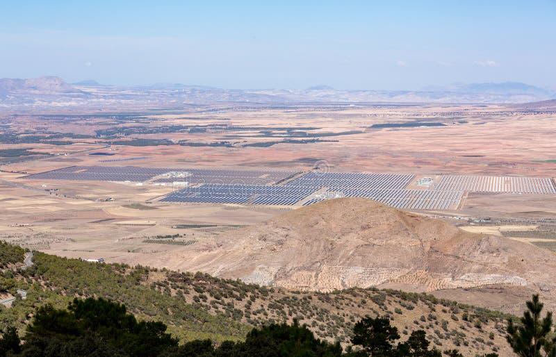 Zonnepanelen in zon onder bergen royalty-vrije stock afbeelding